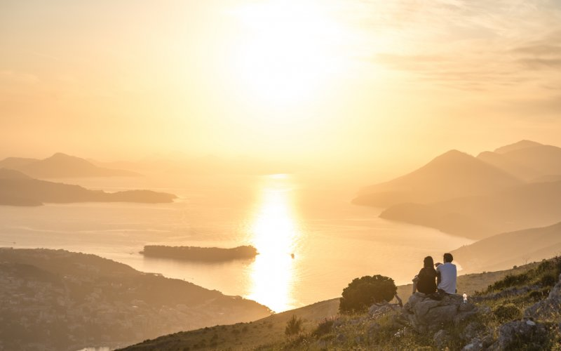 Book Your Eurail/Interrail Adventure at HappyRail | Trip Itineraries for Eurail | Couple enjoying sunset from Mount Sdrj in Dubrovnik, Croatia