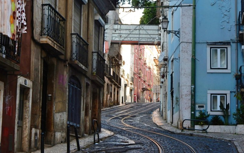 Book Your Eurail/Interrail Adventure at HappyRail | Trip Itineraries for Eurail | Tram tracks in the tiny Streets of Lisbon